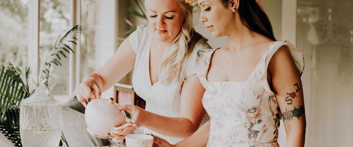 Two ladies holding a high tea